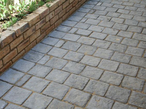 Dark paving on a driveway with retainer wall
